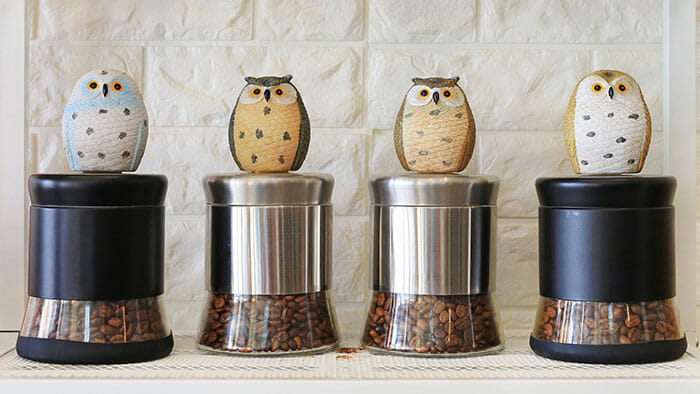 4 coffee containers with toy owls on top